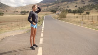 Sporty Woman Standing Alone on the Road Ready to Run