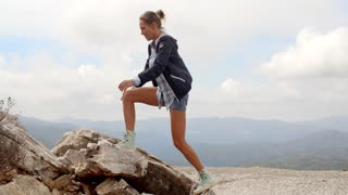 Sporty Woman Standing on Top of Rock, She Wearing Jacket and Jeans Shorts, Slow Motion Video