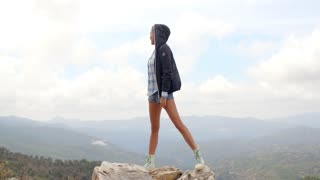 Sporty Woman Standing on Top of Rock With Hands Wide Open, She Wearing Jacket and Jeans Shorts, Slow Motion Video