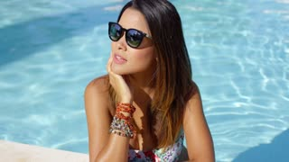 Stylish young woman in sunglasses and bikini standing in the cool water at the edge of a swimming pool looking off to the side with a serious expression.
