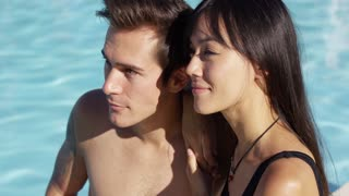 Sunbathing couple sit beside swimming pool and enjoy the sun gently falls on their skin