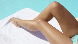 Tanned legs of a young woman sunbathing at the edge of a cool blue swimming pool conceptual of a summer vacation