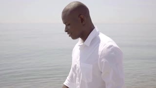Thoughtful African man walking along the sea