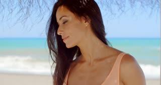 Thoughtful Woman Under Beach Umbrella Looking Afar