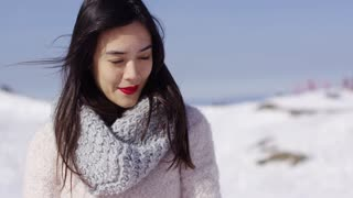 Thoughtful young attractive woman in white sweater on ski slope relaxing on vacation