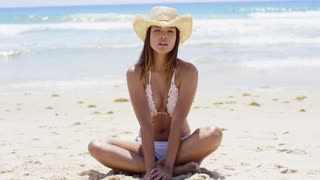 Thoughtful young woman in a bikini sitting cross-legged on a high key tropical beach looking pensively at the camera