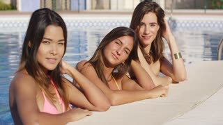 Three attractive women enjoying a summer vacation together relaxing in the cool water of a swimming pool smiling at the camera