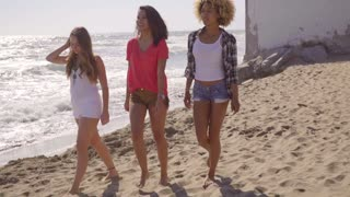 Three attractive young women walking on a beach