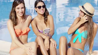 Three beautiful trendy young women relaxing near a swimming pool in a sunhat and sunglasses laughing and chatting on summer vacation