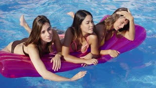 Three bikini clad beauties on a floating device blow kisses at the camera