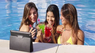Three bikini clad friends toasting pool side while communicating on a nearby computer