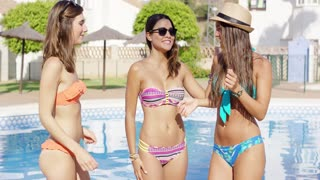 Three cute laughing young women in bikinis standing alongside a swimming pool in a tropical resort relaxing on summer vacation