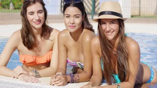 Three gorgeous friendly young women in bikinis relaxing in the cool water of a swimming pool leaning on the tiled surround smiling at the camera