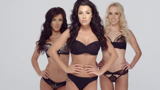 Three gorgeous young fashion models in black lingerie standing side by side close together with their hands on their hips looking at the camera  over grey
