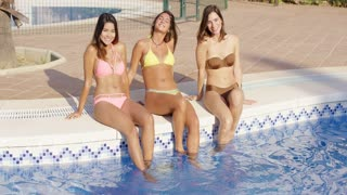 Three happy women sitting on the side of a tropical resort swimming pool in their bikinis smiling at the camera