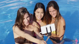 Three happy young women taking their selfie using a stick as they pose together in the cool blue water of a swimming pool on summer vacation.