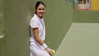 Three Quarter Length Portrait of Smiling Attractive Young Brunette Woman Wearing White Tennis Outfit and Holding Racket While Leaning Against Wall on Sunny Outdoor Court