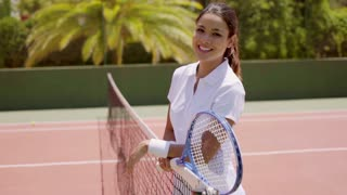 Three Quarter Length Portrait of Smiling Attractive Young Brunette Woman Wearing White Tennis Outfit and Holding Racket While Leaning on Net on Sunny Outdoor Court