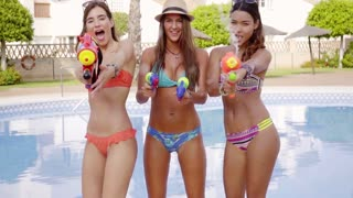 Three sexy bikini girls with water guns standing close swimming pool and shooting water staight into camera.