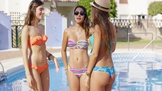 Three sexy trendy women in bikinis posing standing close together at a tropical resort smiling and laughing