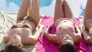 Three sexy young girlfriends sunbathing in bikinis lying together at the edge of a swimming pool tanning in the hot summer sun
