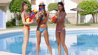 Three sexy young woman in bikinis standing at the edge of swimming pool aiming at the camera with colorful plastic water guns grinning and laughing