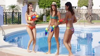 Three sexy young women playing with water guns at the side of a tropical swimming pool in their bikinis while relaxing on summer vacation