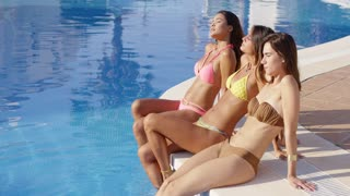 Three sun loving young women in bikinis relaxing at the side of a swimming pool in their bikinis enjoying their summer vacation