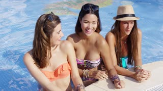 Three trendy young woman relaxing at a pool together laughing and smiling as they cool of in the water in the hot summer sun