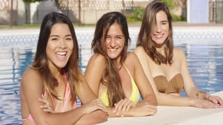 Three vivacious gorgeous young women standing together cooling off in the water of a swimming pool laughing and smiling at the camera