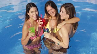 Three vivacious women enjoying cocktails in the cool water of a swimming pool on a hot summer day standing arm in arm laughing and smiling