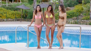 Three young lovely sexy ladies in their bikinis standing leaning against a railing at the edge of a swimming pool chatting and smiling