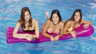 Three young woman floating on an air mattress laughing and kicking their feet splashing around in a swimming pool