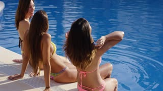 Three young woman relaxing in the summer sun sitting on the tiled surround of a pool in their bikinis sunbathing rear side view