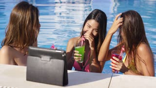 Three young women having fun taking selfies posing in front of a tablet computer on a stand at the edge of a pool laughing and waving.
