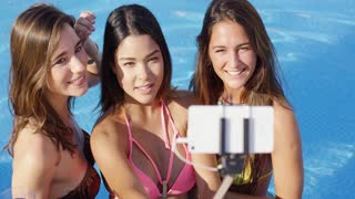 Three young women posing close together in their bikinis taking a selfie in the pool using a selfie stick smiling and laughing