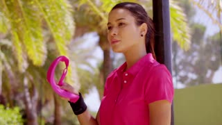 Tired young athletic woman in pink blouse and black wristbands wiping sweat from her brow