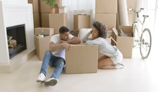 Tired young couple relaxing on the floor on cardboard boxes as they pack up their home to relocate to new premises
