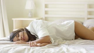 Tired young woman catching a nap lying on top of the rumpled bedclothes on her bed fast asleep