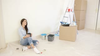 Tired young woman relaxing during renovations to her new home sitting on the floor with a mug of coffee with a stepladder and boxes behind
