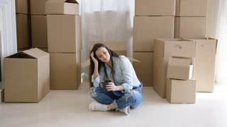 Tired young woman taking a break from moving house sitting cross-legged on the floor with coffee surrounded by boxes