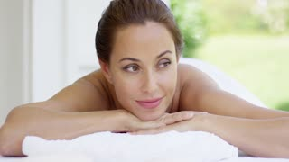 Topless woman looks to one side as she smiles while relaxing on massage table in outdoor spa