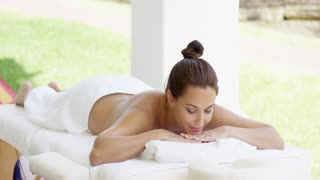 Tranquil spa customer relaxes on table with chin on folded towel in outdoor patio