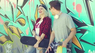 Trendy modern urban couple chatting at a skate park standing leaning against a colorful graffiti covered wall with their skateboards in the summer sun