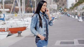 Trendy relaxed young woman talking on a mobile
