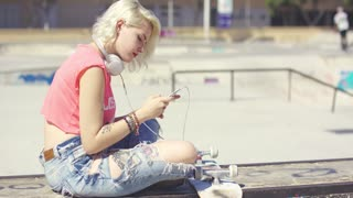 Trendy young blond woman at a skate park sitting on a graffiti covered wall with her skateboard choosing a tune to listen to on her mobile phone.
