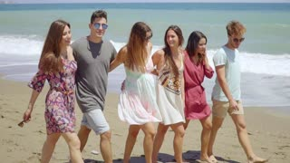 Trendy young friends strolling barefoot on a beach