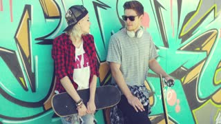 Trendy young skateboarders standing chatting leaning against a colorful graffiti wall with a young woman in a baseball cap and handsome young man in sunglasses