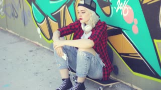Trendy young urban woman wearing a baseball cap and torn jeans sitting waiting on her skateboard in front of a colorful graffiti covered wall