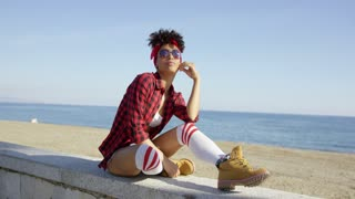 Trendy young woman relaxing on a beachfront wall on a promenade overlooking the sea in skimpy shorts sunglasses bandanna and red plaid shirt enjoying the summer sun.